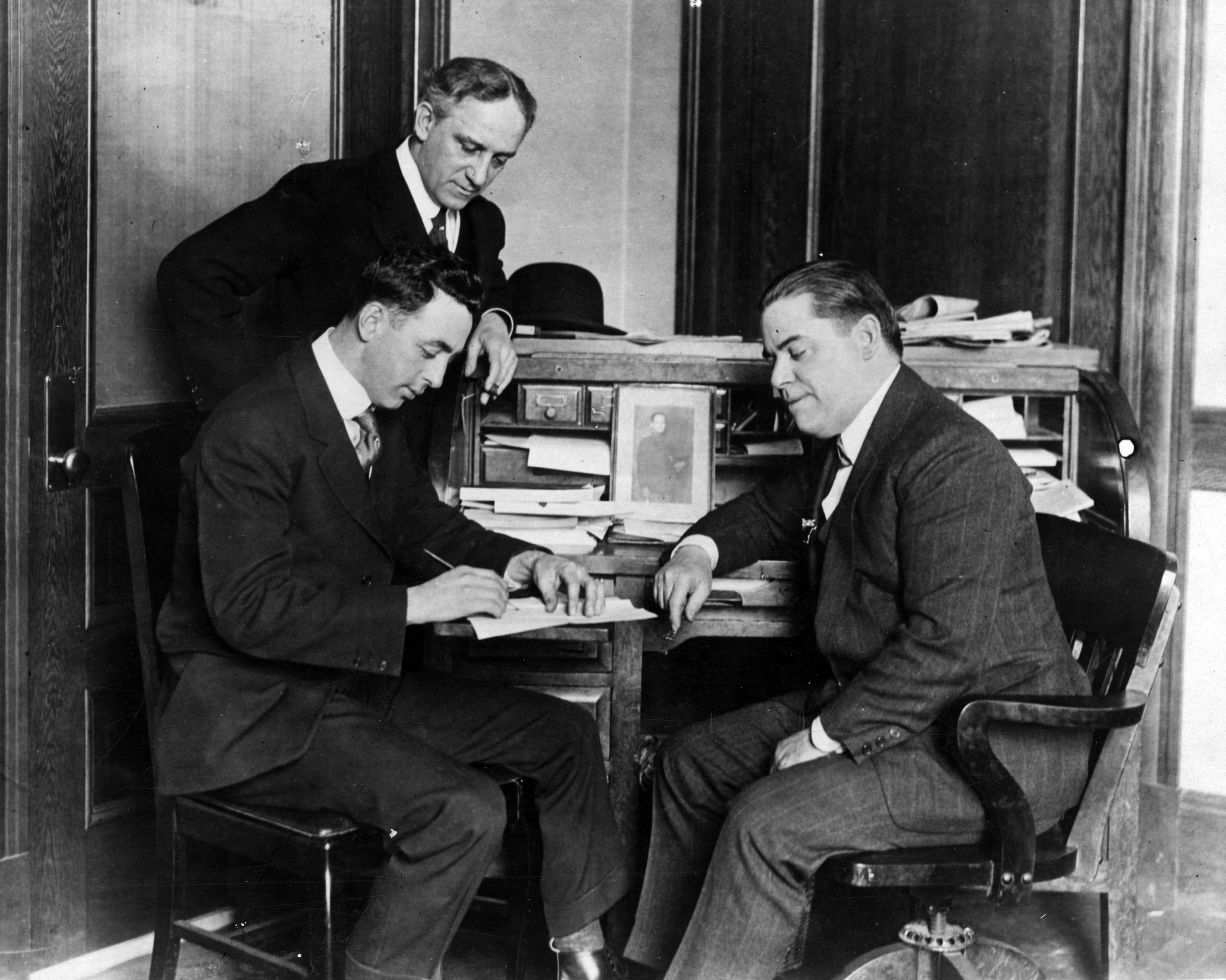 Red Sox player-manager, left, signs his 1917 contract as owner Frazee looks on.